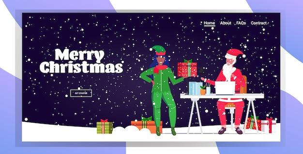 Święty mikołaj za pomocą laptopa afroamerykanin kobieta elf pomocnik trzymający prezent pudełko boże narodzenie nowy rok święta uroczystość koncepcja śniegu strona docelowa