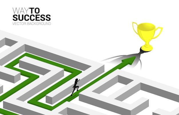 Sylwetka biznesmen biegnie na strzałkę ze ścieżką trasy, aby wyjść z labiryntu do złotego trofeum. koncepcja biznesowa rozwiązywania problemów i strategii rozwiązania