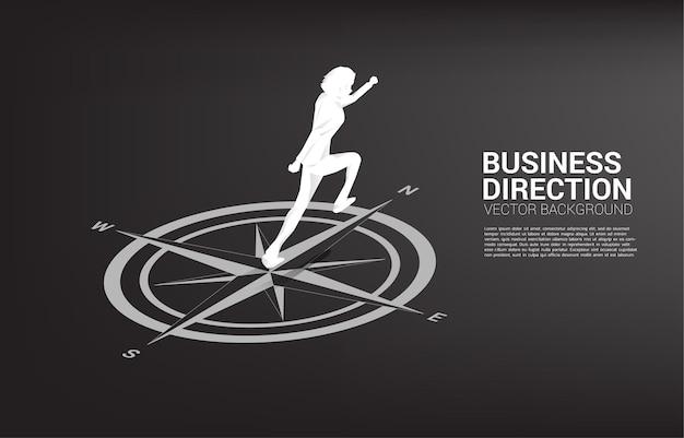 Sylwetka biznesmen działa na środku kompasu na podłodze.