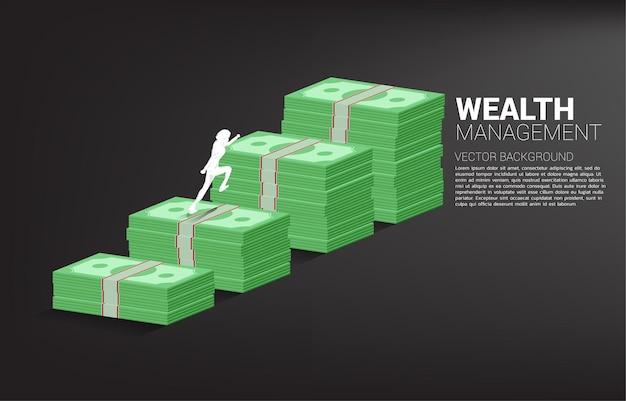 Sylwetka biznesmen działa na wykresie wzrostu ze stosem banknotów.
