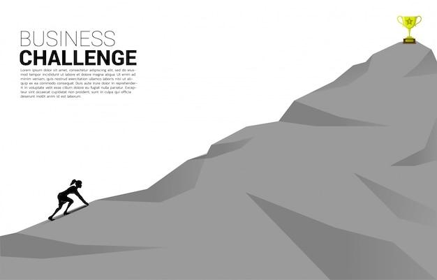 Sylwetka biznesmen gotowy do uruchomienia trofeum na szczycie góry.