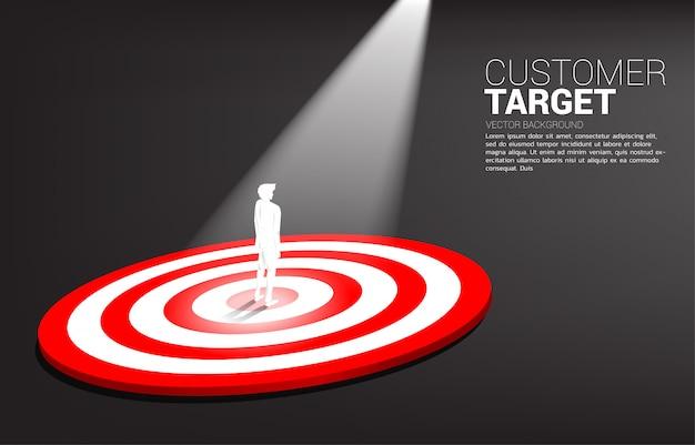 Sylwetka biznesmen pozycja na centrum dartboard z punktu światłem