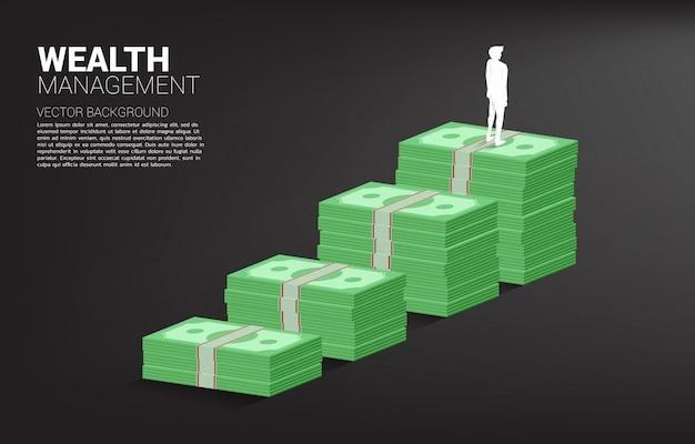 Sylwetka biznesmen pozycja na górze wzrostowego wykresu z stertą banknot
