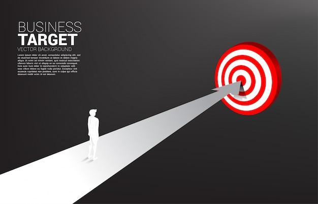 Sylwetka biznesmen pozycja na trasie ześrodkowywać dartboard tło