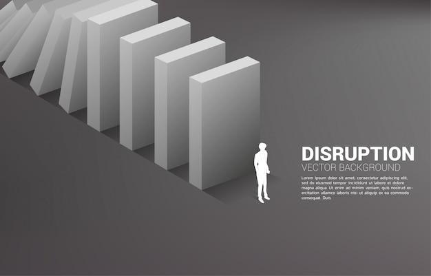Sylwetka biznesmen pozycja przy końcówką domina zawalenie się. pojęcie zakłócenia w branży biznesowej