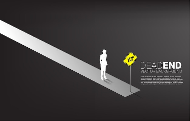 Sylwetka biznesmen stojący na końcu drogi z oznakowaniem ślepy zaułek.
