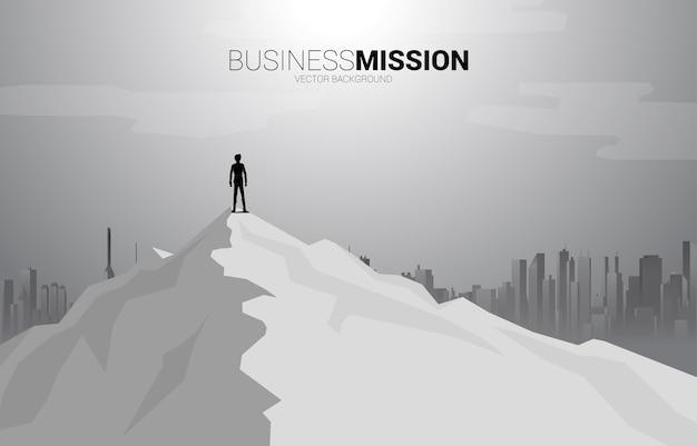 Sylwetka biznesmen stojący na szczycie góry i tła miasta. koncepcja celu, misji, wizji, sukcesu na ścieżce kariery.