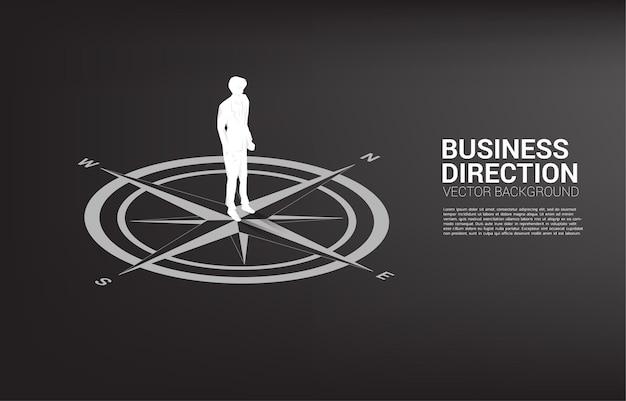 Sylwetka biznesmen stojący w środku kompasu na podłodze.