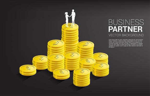 Sylwetka biznesmena i bizneswomanu uścisk dłoni na górze sterty monet. koncepcja partnerstwa i współpracy biznesowej.