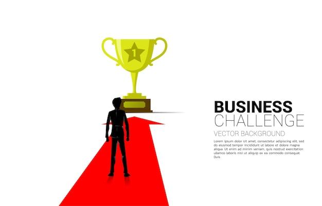 Sylwetka biznesmena na strzałkę przejść do złotego trofeum. koncepcja kierunku biznesowego i wizji misji