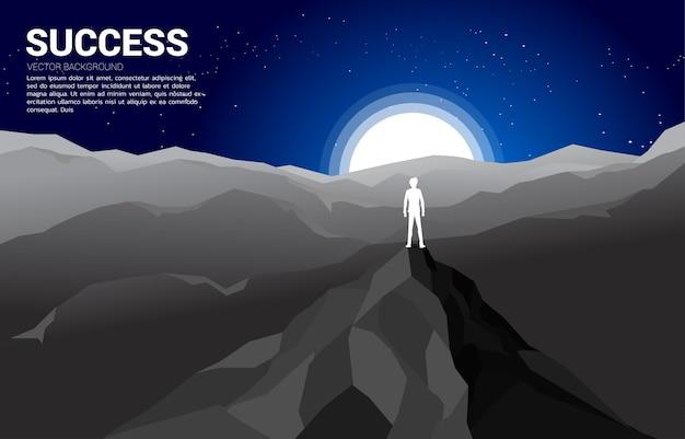 Sylwetka biznesmena na szczycie góry. ilustracja sukcesu w karierze i misji