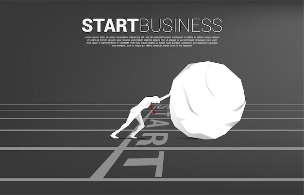 Sylwetka biznesmena pchanie skały z linii startu. pojęcie wyzwania biznesowego i ciężkiej pracy.