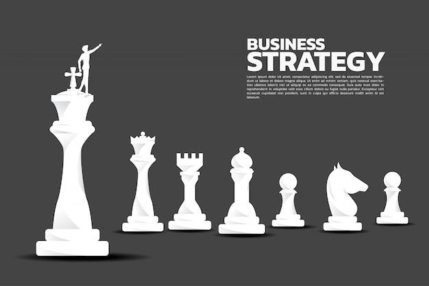 Sylwetka biznesmena punkt naprzód z szachowym kawałkiem.