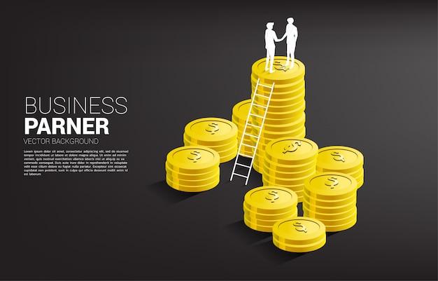 Sylwetka biznesmena uścisk dłoni na górze sterty monet z drabiną. koncepcja partnerstwa i współpracy biznesowej.