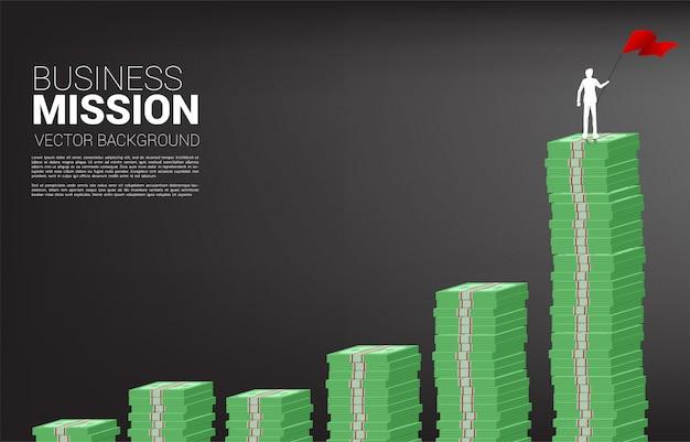 Sylwetka biznesmena z czerwoną flagą stoi na wykresie wzrostu ze stosu banknotów. koncepcja sukcesu firmy i ścieżki kariery.