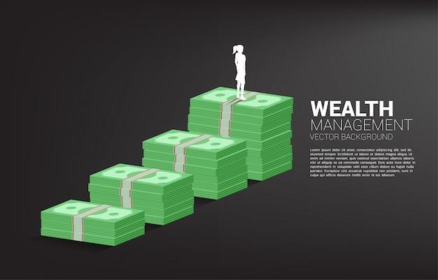 Sylwetka bizneswoman pozycja na górze wzrostowego wykresu z stertą banknot