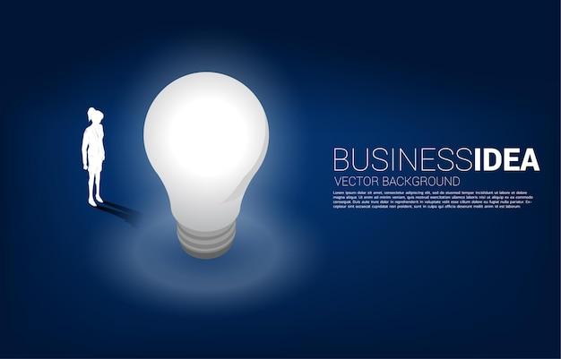 Sylwetka bizneswoman stojącej z żarówką. baner biznesowy kreatywny pomysł i rozwiązanie.