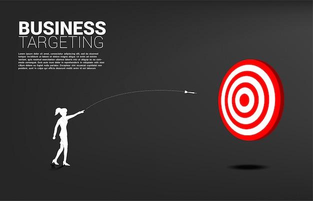 Sylwetka bizneswoman wyrzuca strzałkę dart, aby trafić w tarczę. koncepcja biznesowa targetowania i wizja klienta.