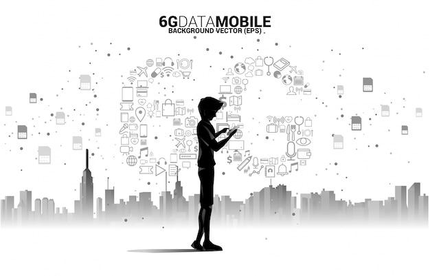 Sylwetka człowieka z telefonem komórkowym i technologią danych 6g z ikony funkcji online. koncepcja globalnej sieci telekomunikacji mobilnej.