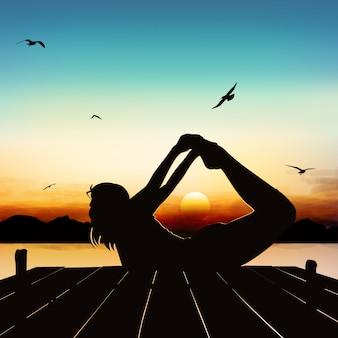 Sylwetka dziewczyny jogi postawy w zmierzchu.