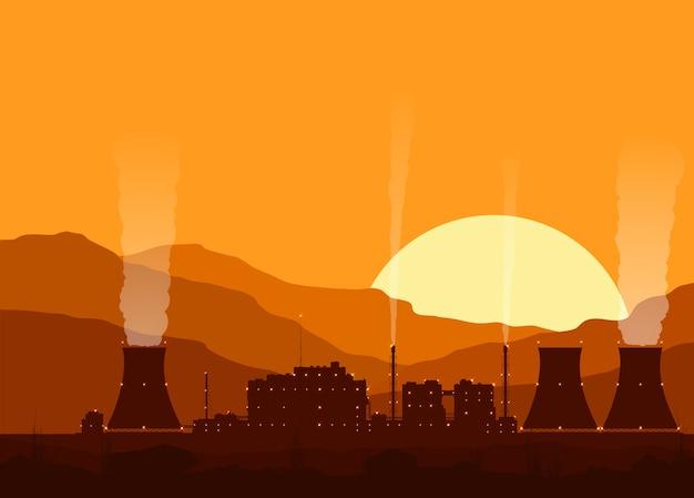 Sylwetka elektrowni jądrowej ze światłami o zachodzie słońca w górach.