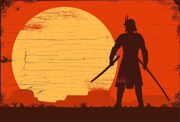 Sylwetka japońskiego samuraja z mieczem stojącego o zachodzie słońca