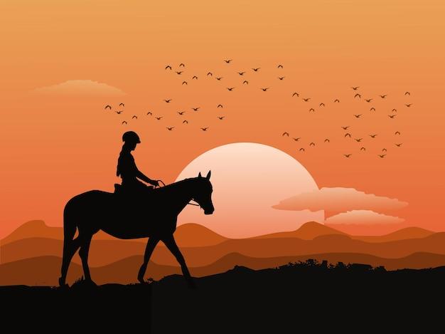Sylwetka kobiety na koniu na szczycie góry z zachodem słońca w tle.