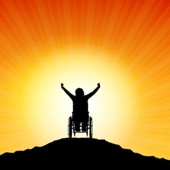 Sylwetka kobiety na wózku inwalidzkim z podniesionymi rękami w sukces