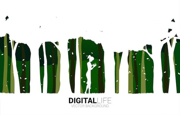 Sylwetka kobiety use telefon komórkowy w zieleń parku. koncepcja cyfrowego życia z naturalnym
