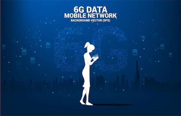 Sylwetka kobiety z telefonem komórkowym i technologią danych 6g z ikony funkcji online. koncepcja globalnej sieci telekomunikacji mobilnej.