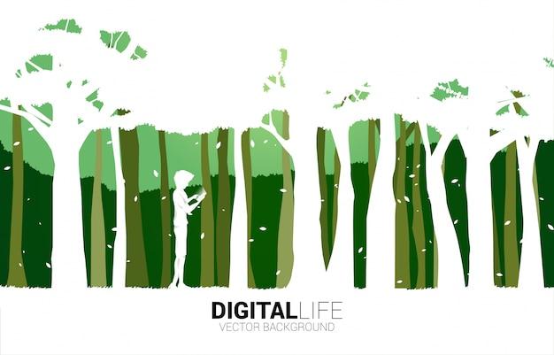 Sylwetka mężczyzna use telefon komórkowy w zieleń parku. koncepcja cyfrowego życia z naturalnym