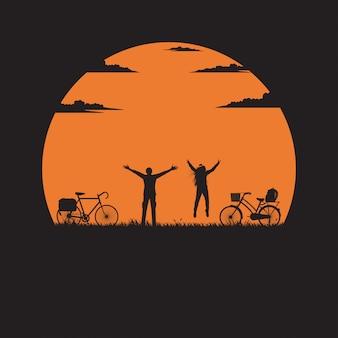 Sylwetka mężczyzny i kobiety stoją podnosząc rękę na łące z zachodem słońca