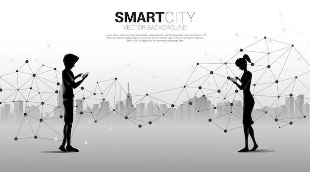 Sylwetka mężczyzny i kobiety używa telefonu komórkowego z 5g futurystyczną kropką wielokąta połącz linię z tłem miasta. koncepcja pracy zdalnej z domu i technologii.