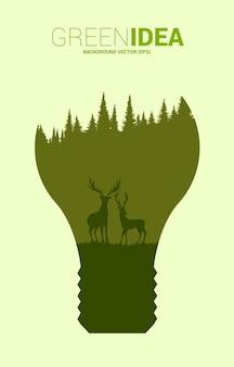 Sylwetka wielkiego jelenia i drzewa w żarówce. tło dla zielonego pomysłu i ochrony środowiska.