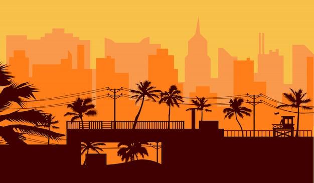 Sylwetki drzewko palmowe na plaży i pejzaż miejski pod zmierzchu niebem