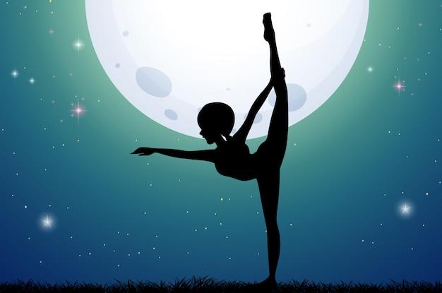 Sylwetki kobieta robi joga przy nocą
