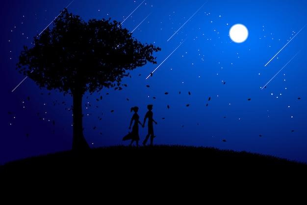 Sylwetki kochanek pary mienia ręki odprowadzenie pod dużym drzewnym tłem.