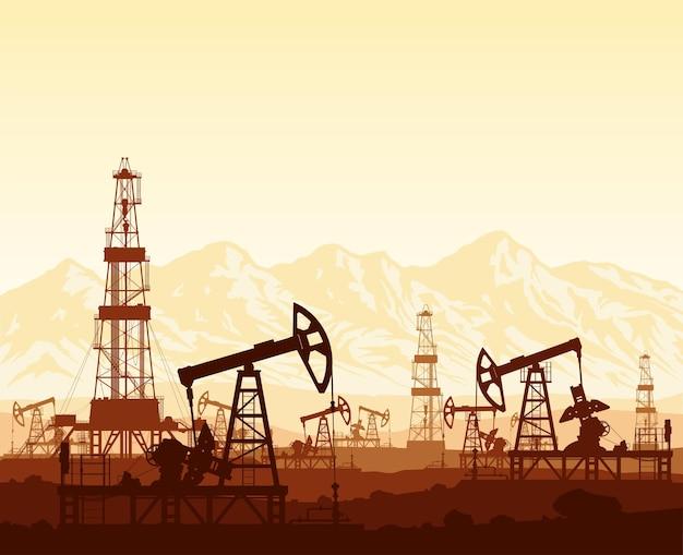 Sylwetki pomp naftowych i platform wiertniczych na dużym polu naftowym na ogromnym paśmie górskim o zachodzie słońca.