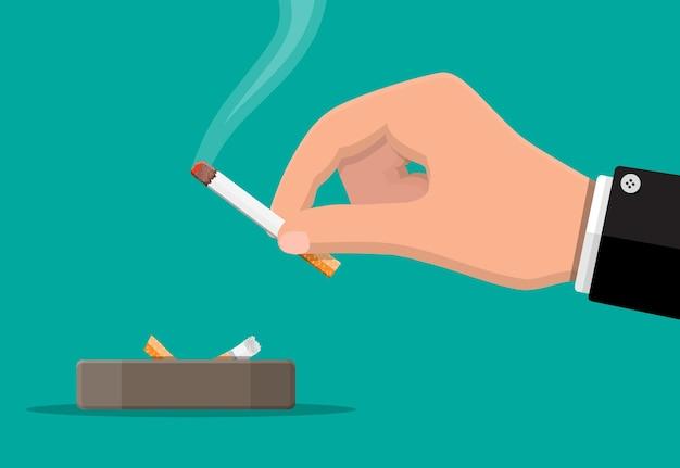 Szara ceramiczna popielniczka pełna palących się papierosów. naczynia do palenia. papieros w ręku. ilustracja wektorowa w stylu płaski