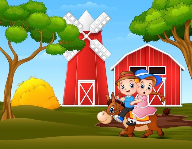 Szczęśliwa chłopiec i dziewczyna jedzie konia w gospodarstwo rolne krajobrazie