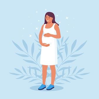 Szczęśliwa ciąża i macierzyństwo. piękna młoda kobieta w ciąży trzyma jej brzuch. mama spodziewa się porodu