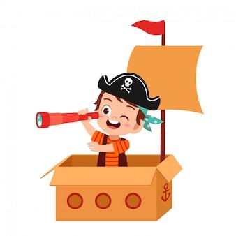 Szczęśliwa dzieciak chłopiec sztuki zabawki statku karton