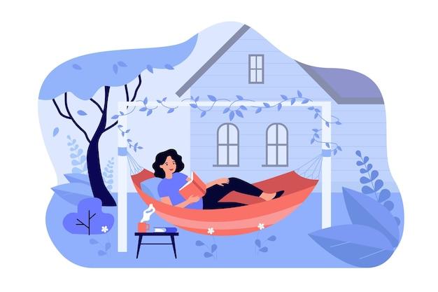 Szczęśliwa dziewczyna relaksujący, leżąc w hamaku i czytając książkę