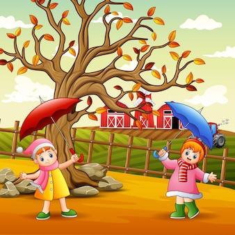 Szczęśliwa dziewczyna trzyma parasol w krajobrazie gospodarstwa