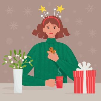 Szczęśliwa dziewczyna w świątecznych ubraniach i dekoracjach pije gorący napój z piernikowymi ciasteczkami