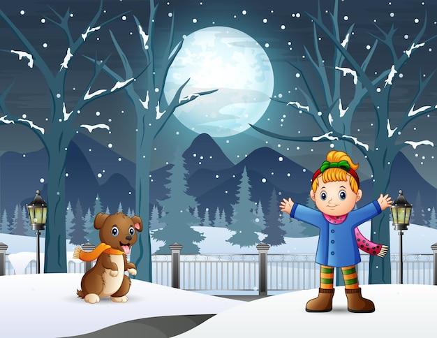 Szczęśliwa dziewczynka bawi się ze swoim zwierzakiem w zimową noc