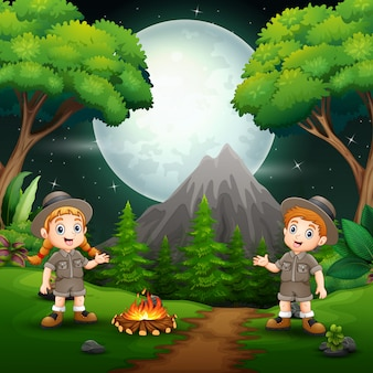Szczęśliwa harcerz chłopiec i dziewczyna z ogniskiem przy nocą