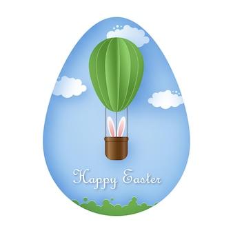 Szczęśliwa kartka wielkanocna z królikiem latającym na zielonym balonie na ogrzane powietrze na tle błękitnego nieba