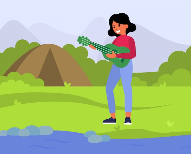 Szczęśliwa kobieta bawić się gitarę w wsi