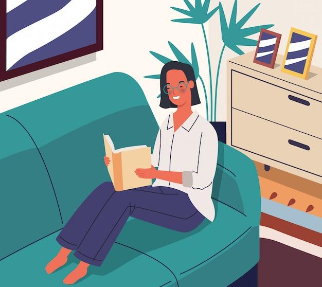 Szczęśliwa kobieta czyta książkowego obsiadanie na kanapie w pokoju.